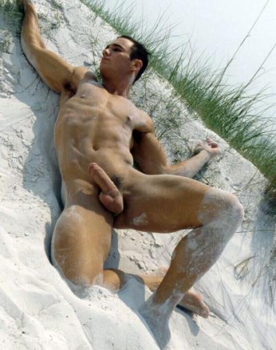 Парень атлетического телосложения лежит голый на пляже 7 фото
